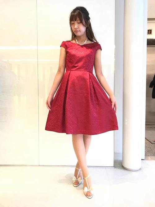 赤ジャガードドレスと白ミュールとネックレスのコーデの女性