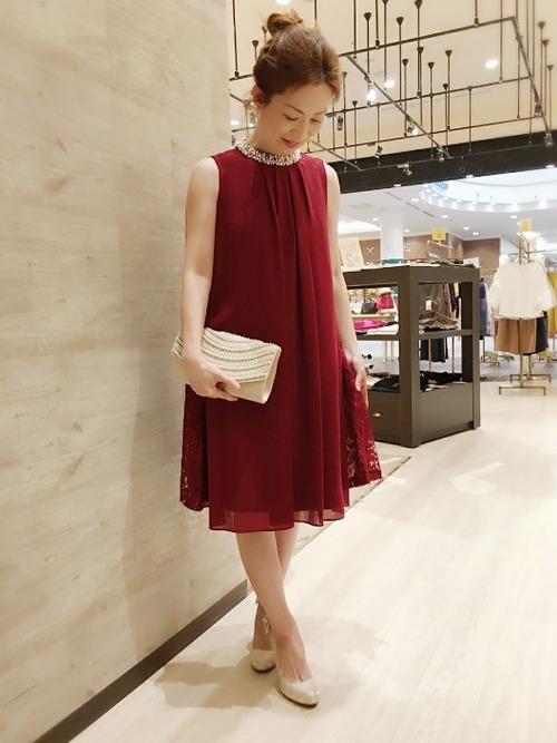 ビジュ-付きAライン赤ドレスと白パンプスとパーティバックのコーデの女性