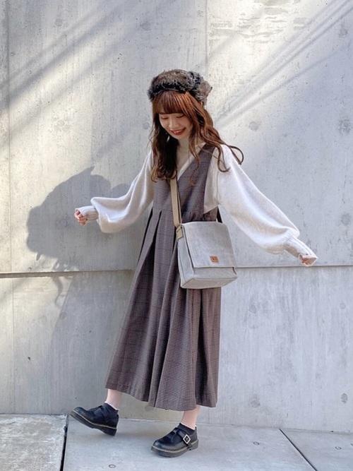 ハイネックボリューム袖ニットとプリーツジャンパースカートとブラックシューズのコーデの女性