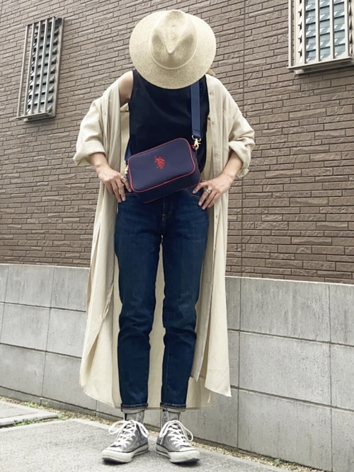 ベージュ中折れ帽とストレートデニムパンツにグレーコンバースハイカットスニーカーを履いた女性