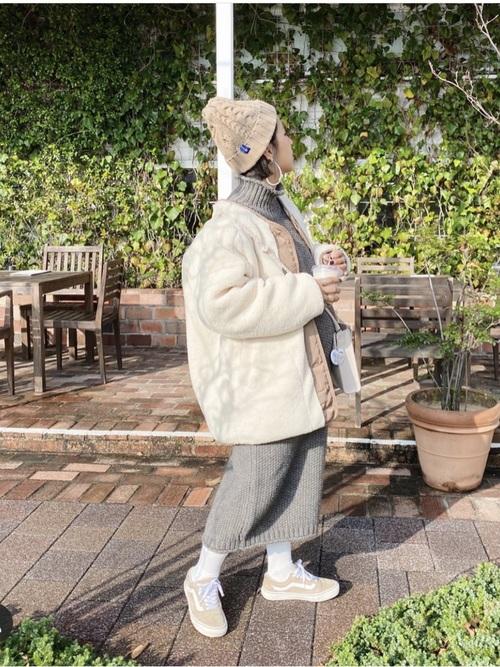 ベージュビーニーキャップとボアコートにベージュVANSオールドスクールを履いた女性