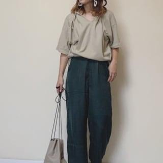 ベージュ半袖キーネックパーカーと緑タックワイドパンツにアイボリーフラットシューズを履いた女性