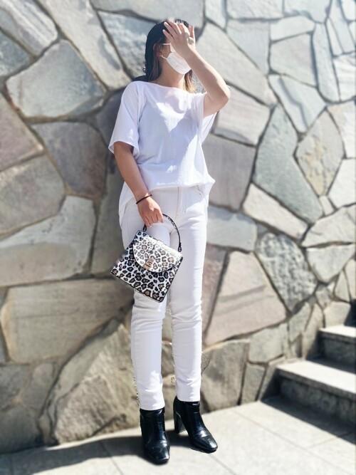 ショートスリーブ白Tシャツと白スキニーデニムパンツにかっちりフォルムバッグを合わせた女性