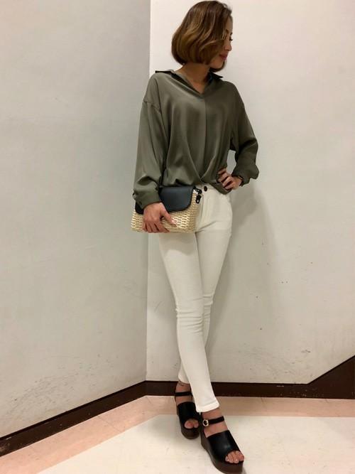 カーキ裾タックシャツと白スキニーに黒ウェッジソールサンダルを履いた女性
