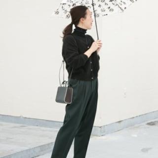 黒タートルニットセーターとモスグリーンパンツにモノトーン花柄日傘を合わせた女性