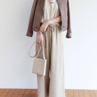 ノーカラースエード茶色ライダースとベージュロゴTシャ`ツにリネンワイドパンツを履いた女性