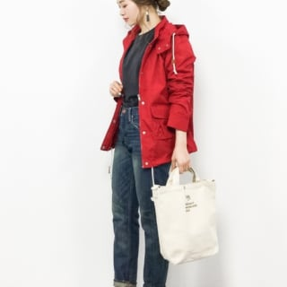 赤マウンテンパーカーとデニムパンツにトートバッグを合わせた女性
