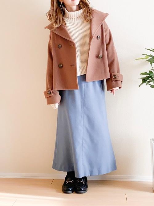 ベージュショートコートとマーメイド青ロングスカートに白ハイネックニットを合わせた女性