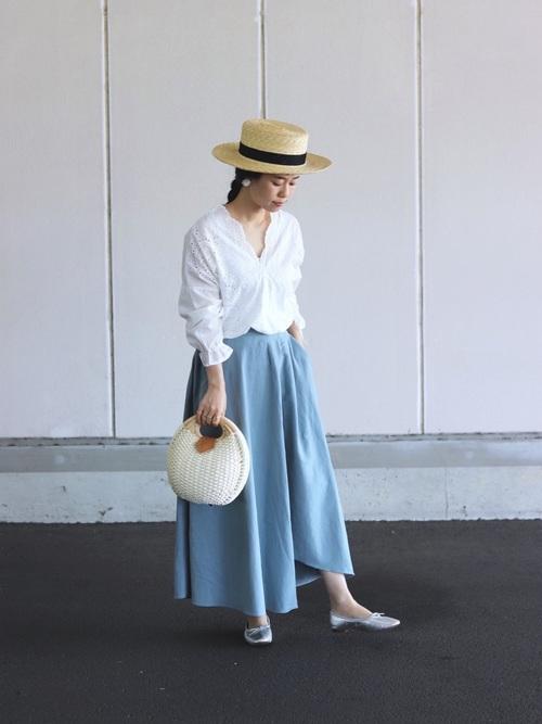 Vネックブラウスとストローハットに淡め青ロングスカートを履いた女性