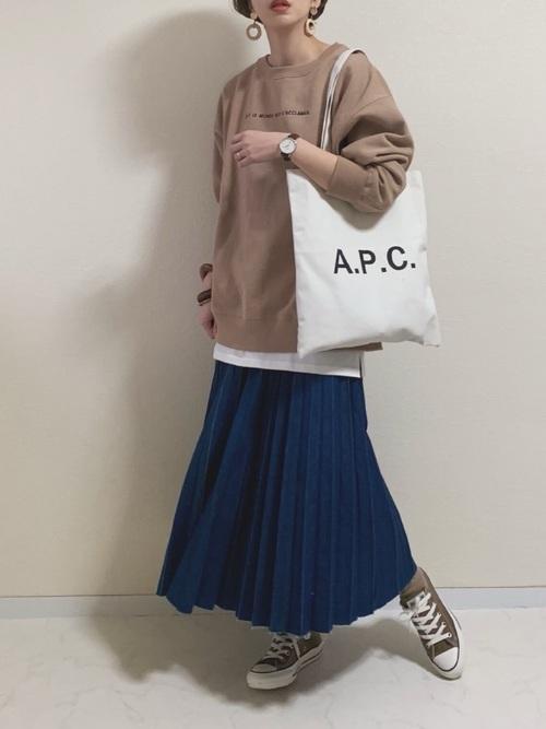 ベージュパーカーとプリーツ青ロングスカートにブラウンスニーカーを履いた女性