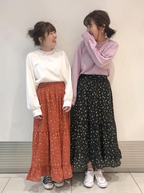 色違いカットソーと花柄ティアードスカートに色違いスニーカーを履いた女性