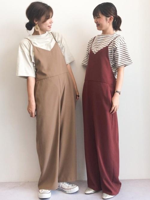 色違い渋色サロペットとオーバーサイズTシャツにコンバース白スニーカーを履いた女性