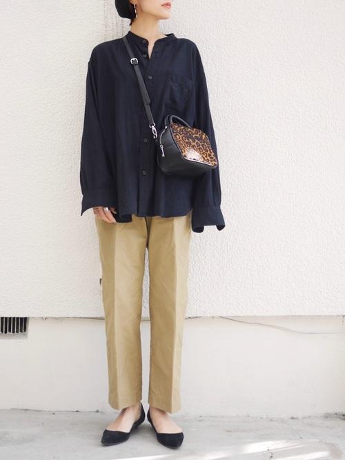 フランネルスタンドカラーシャツとベージュチノパンにパンプスを履いた女性