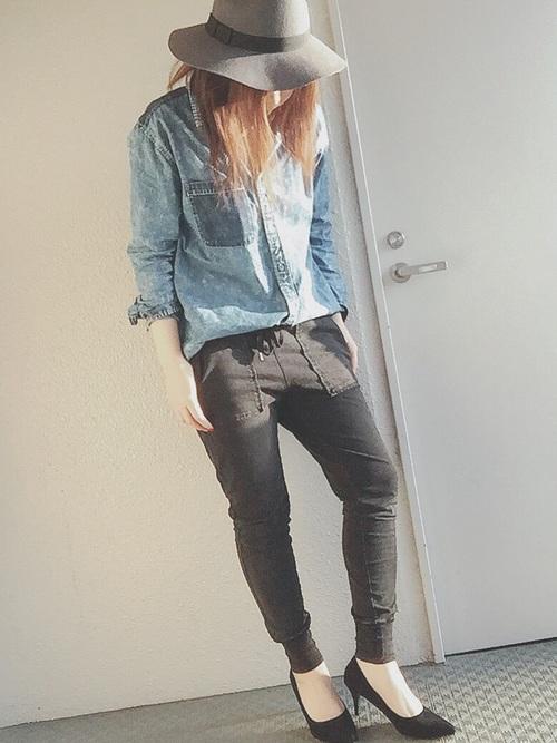 ブルーシャツとスウェットイージーパンツにシンプルブラックパンプスを履いた女性