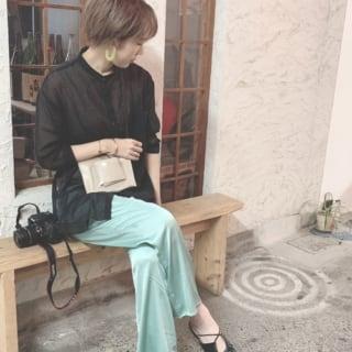 サテン素材パンツとヌーディカラーウエストバッグにラウンドカットギャザーストラップ黒パンプスを履いた女性
