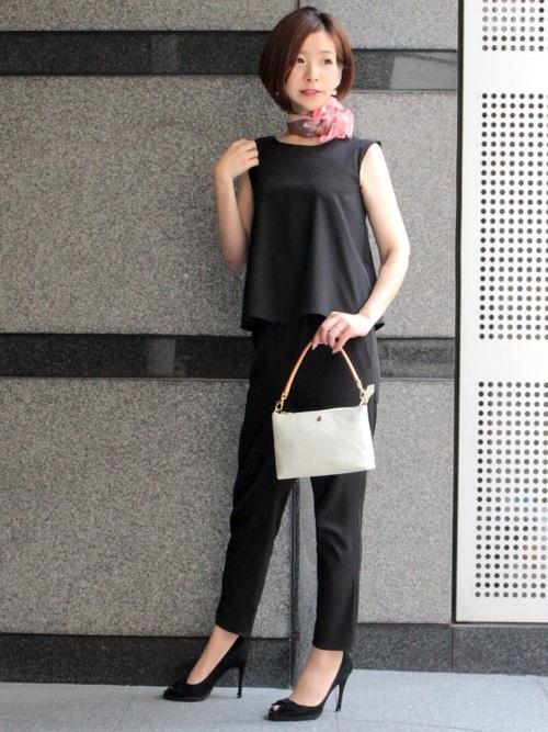 ピンクシルクスカーフとオールインワンサロペットに高めヒールオープントゥ黒パンプスを履いた女性