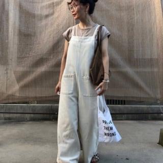 ダブルポケットロングワンピースとベージュチノパンツにベッコウフレーム眼鏡を合わせた女性