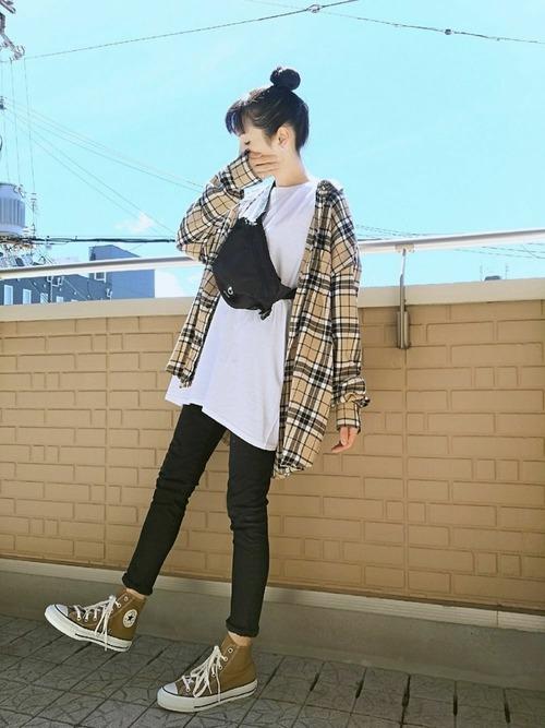 ハイウエストスキニーとシンプルTシャツにハイウエストスキニーデニムパンツを履いた女性