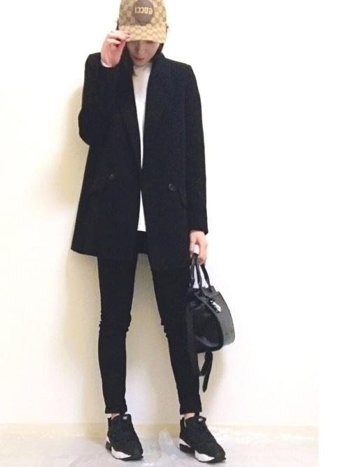 黒テーラードジャケットと白プルオーバーと黒タイトパンツのコーデの女性