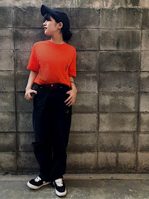 ポケット刺繍デザインTシャツと黒ストレートデニムパンツと黒スニーカーのコーデの女性