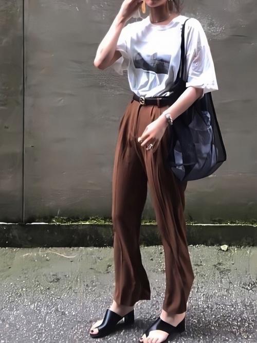 プリント白Tシャツとグッチの黒カーフレザーベルトとブラウンハイウエストピンタックポイントワイドスラックスのコーデの女性