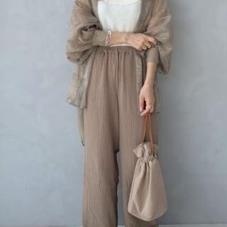 シースルースタンドカラーシャツとベージュガーゼワイドパンツと巾着バッグのコーデの女性