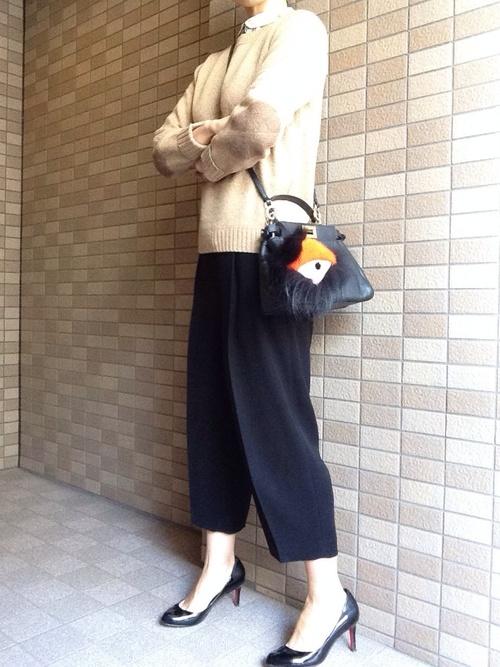 ルブタンの黒パンプスと黒ショルダーバッグにワイドクロップドパンツを履いた女性