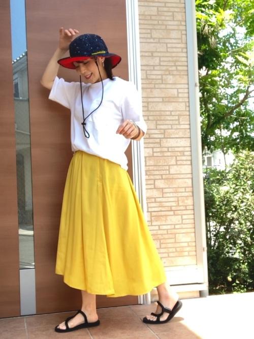 半袖白シャツとボーダーTシャツとポリエステルイレギュラーヘムスカートにモンベルのサンダルを履いた女性