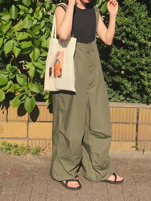 ブラックタンクトップとグリーンオールインワンにモンベルのサンダルを履いた女性