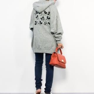 バッグ刺繍ミッキーパーカーとスキニージーンズにフラップ2WAYショルダーバッグを合わせた女性