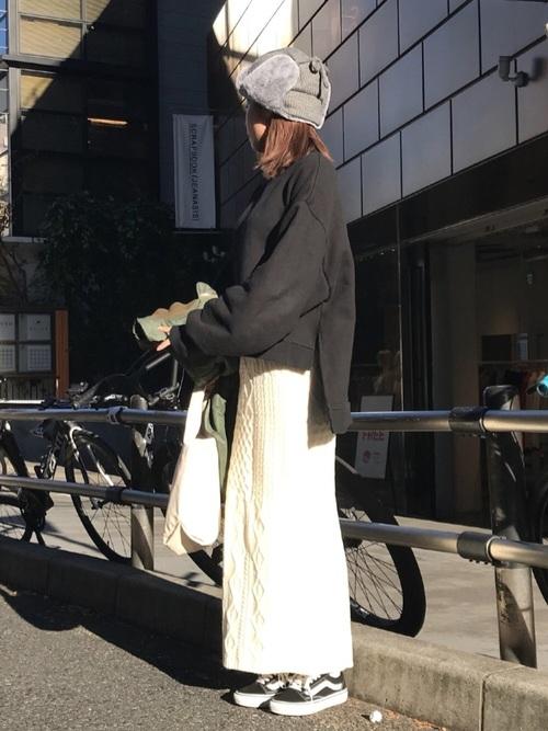 黒ビッグスリーブプルオーバーと白ニットタイトロングスカートに黒ローカット厚底スニーカーを履いた女性