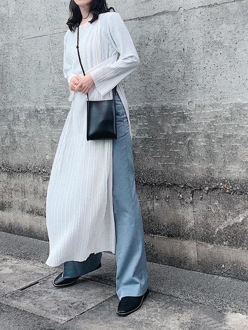 白アシンメトリーラップワンピースとセミブーツカットスラックスにアウトソールスパンブーツを履いた女性