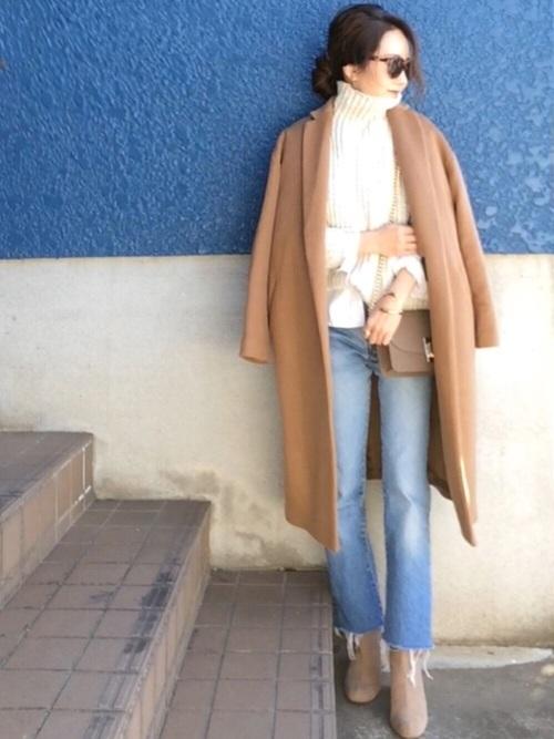 白タートルネックニットとブルーデニムパンツにベージュスエードチェーンショルダーバッグを合わせた女性