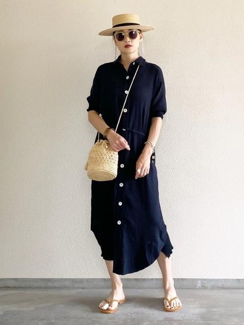 シェルボタンシャツドレスとブラウンスエードビーチサンダルにベージュカゴ巾着ショルダーバッグを合わせた女性