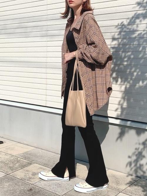 ビックシルエットチェックシャツとリブフレアパンツにベージュキャンバス巾着ショルダーバッグを合わせた女性