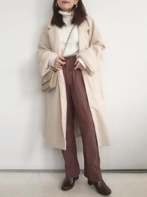 ベージュウエストマークチェスターコートとブラウンスラックスパンツにベージュダイヤ柄ステッチショルダーバッグを合わせた女性