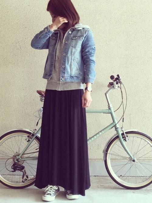 デニムジャケットとフルジップパーカーにロングスカートを履いた女性