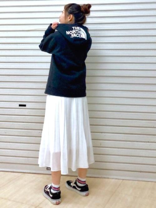 ロゴフルジップパーカーとチュールスカートにスニーカーを履いた女性