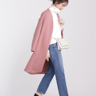 ピンクコートを羽織りデニムを履いた女性