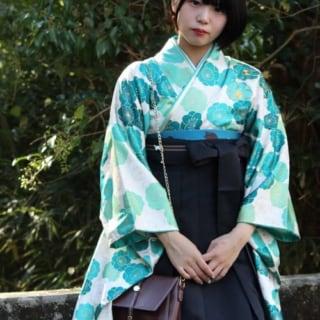 白地水色花柄着物と紺袴にレザーバッグを履いた女性