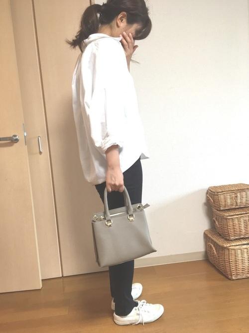 白コットンシャツと黒スキニーパンツにスペルガの白スニーカーを履いた女性