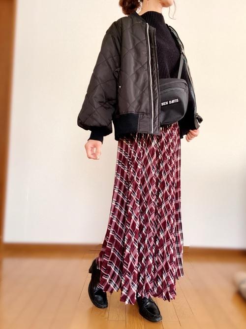 黒タートルニットにキルティングダウンジャケットを羽織り、赤黒チェックのプリーツスカートを合わせ黒のウエストバッグとローファーを用いたコーデ