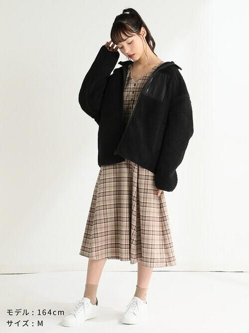 茶色ベースのチェック柄ワンピに黒のブルゾンを羽織り、茶色ソックスと白スニーカーを合わせたコーデ