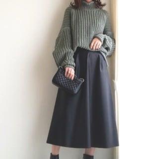 緑のニットに黒のスカートのコーデ