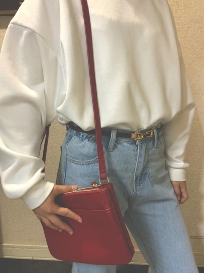 白の長袖トップスにデニムを合わせ、赤のショルダーバッグを用いたコーデ
