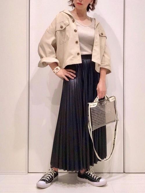 ベージュのインナにベージュのアウターを羽織り、黒レザープリーツスカートを合わせ、クリアショルダーバッグと黒スニーカーを用いたコーデ