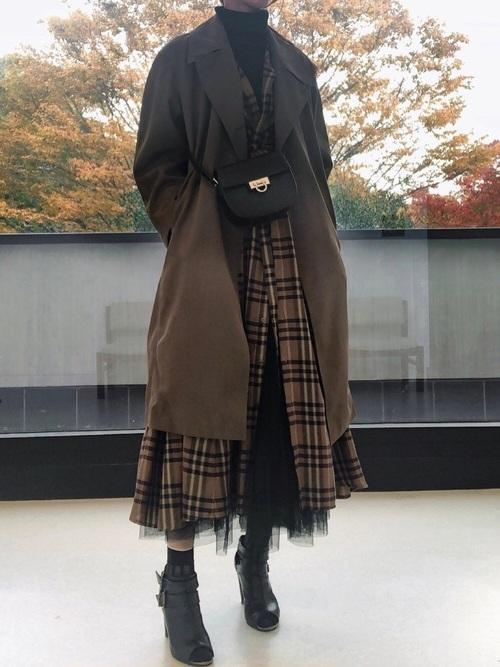 黒のタートルにブラウンチェックのワンピースとブラウンロングジャケットを羽織り、黒のチュールスカートと黒のブーティーを合わせたコーデ