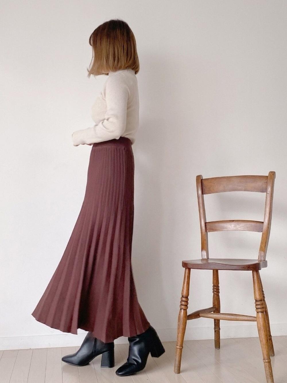 白のトップスにプリーツスカートとファインフィットスクエアトゥヒールブーツのコーデ