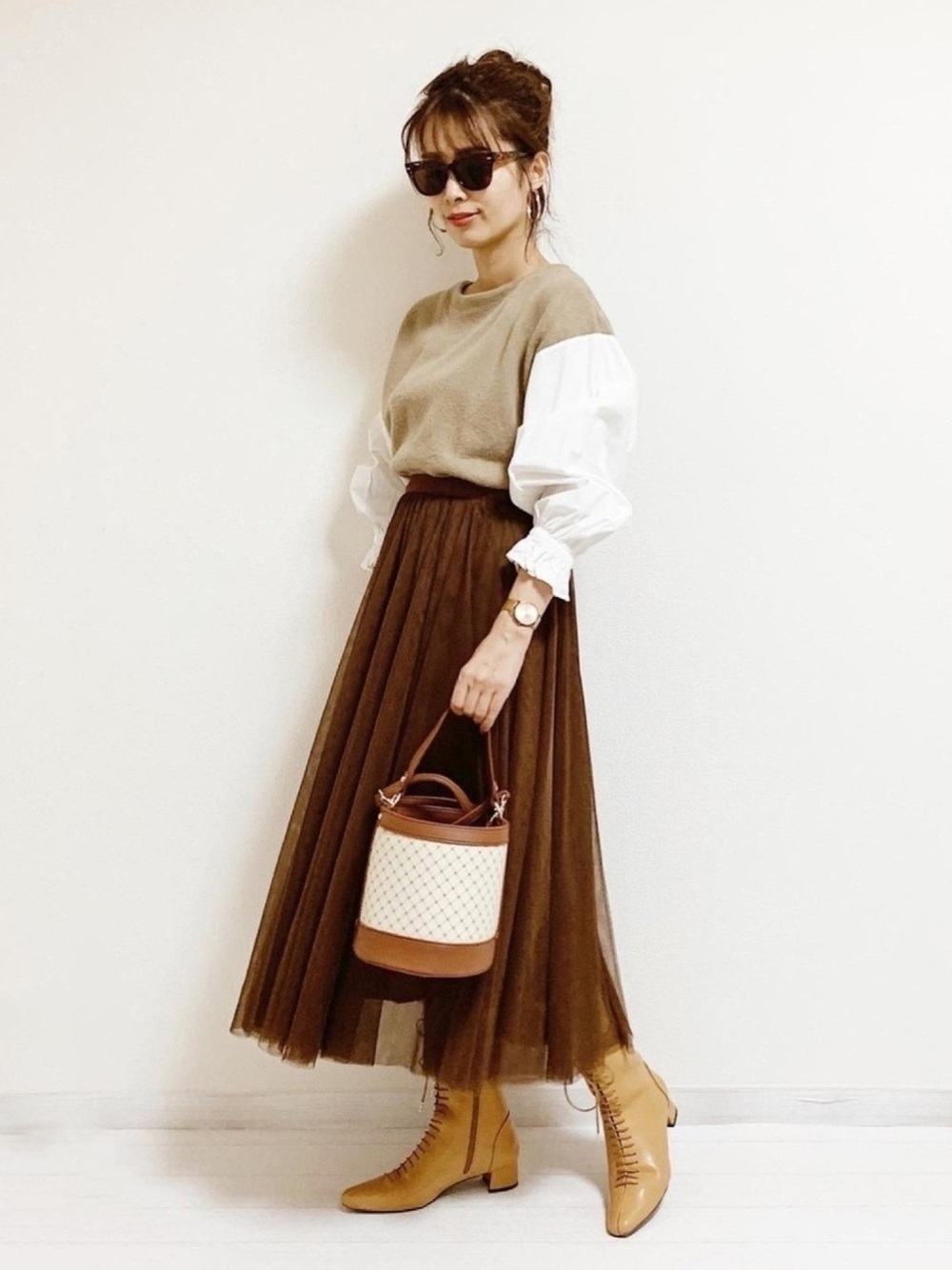 ベージュのトップスにブラウンのスカートとバケツバッグのコーデ