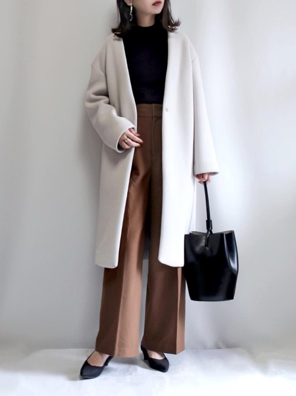 黒のタートルネックにブラウンパンツと白コートのコーデ